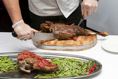 Cook cut up roast lamb leg — Stock Photo
