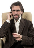 Angry businessman sitting with mobile phone — Stock Photo