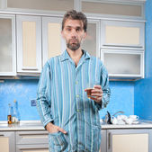 Drunk man standing in pajamas with glass — Stock Photo