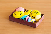 Box with magnetic smiles on tabletop — Stock Photo