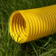 Yellow plastic pipe on green grass — Stock Photo