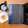Netbook with coffee and donut top view — Stock Photo