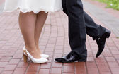 Shoes of a bride and groom walking by the pavement city — Stock Photo
