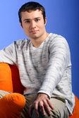 年轻的男模特坐在橙色椅子上蓝色隔离 — 图库照片