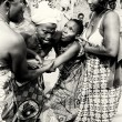 Stock Photo: Three ladies from Togo help their friend which loses control under voodoo enchantment