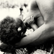 A little baby from Togo drinks milk from the mother brest — Stock Photo