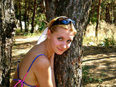 Beautiful girl smiles near the tree — Photo