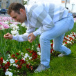 Young man smells the flowers — Stock Photo