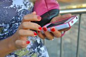 Girl send sms message using her white and pink iPhone 4S — Stock Photo