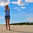 Beautiful girl poses on the sand — Stock Photo