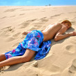 Beautiful naked girl in a blue tissue sleeps on the sand — Stock Photo