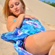 Beautiful naked girl in a blue tissue is on the sand — Stock Photo