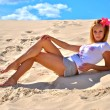 Young sexy model poses over the sand — Stock Photo