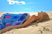 Bella ragazza nuda in un tessuto blu è sulla sabbia — Foto Stock