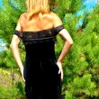 Sexual girl from behind in a black dress near a fir-tree — Stock Photo