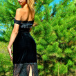 Sexual girl in a black dress near a fir-tree — Stock Photo