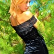 Stock Photo: Amazing blonde sexual girl in a black dress poses near a fir-tree