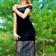Lovely blonde sexual girl in a black dress poses near a fir-tree — Stock Photo