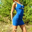 Lovely blonde sexual girl in a blue dress poses near a fir-tree — Stock Photo