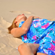 Sexual blond model in a blue tissue sleeps on the sand — Stok fotoğraf