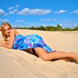 Beautiful sexual naked blond model covered with a blue tissue on the sand — Stock Photo