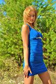 Bella bionda ragazza sessuale in un abito blu pone vicino a un abete — Foto Stock