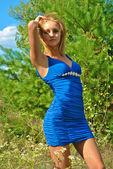 Schönes Blondes sexuelles Mädchen in einem blauen Kleid stellt in der Nähe eine Tanne — Stockfoto