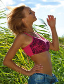 Sexual blond girl poses in shorts in reeds — Stock Photo