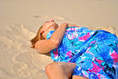 Sexual blond model in a blue tissue sleeps on the sand — Stock Photo