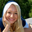 Stock Photo: Beautiful blond girl plays with a camera smiling