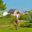 Beautiful sexual blond girl poses in a green field with a house behind — Stock Photo