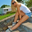 Beautiful sexual blond girl sits on the stone stairs — Stock Photo