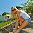 Beautiful sexual blond girl sits on the stone stairs — Stock Photo #12382046