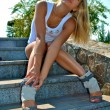 Beautiful sexy blond girl sits on the stone stairs — Stock Photo
