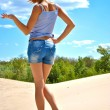 Sexual blond girl from behind in jeans shorts stays on the sand in a shiny day — Stock Photo