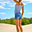 Foto Stock: Sexual blond girl from behind in jeans shorts stays on sand in shiny day