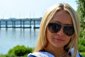 Cute blond girl in sun glasses poses for the camera in front of the bridge — Stock Photo