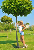 Beautiful sexual blond girl poses near a green tree — Stock Photo