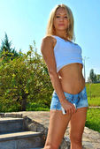 Beautiful sexy blond model show her sexuality on the stairs wearing jeans shorts — Stock Photo