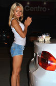 Beautiful young sexy blond girl eats an ice cream on the back of the car — Stock Photo