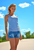 Sexual blond girl in jeans shorts stays on the sand in a shiny day — Stock Photo