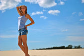 Sexual blond girl stays on the sand in a shiny day — Stock Photo