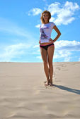 Beautiful sexual blond girl stays on the sand in panties — Stock Photo