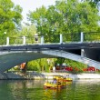 Stock Photo: Take walk on water cycles under bridge on lake in park