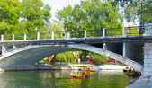 Take a walk on the water cycles under the bridge on the lake in the park — Stock Photo