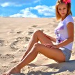 Stock Photo: Beautiful sexy blond girl makes poses on sand