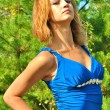 Beautiful sexual blond female model poses in a blue dress — Stock Photo