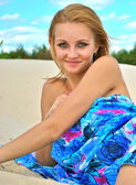 Beautiful pretty sexy blond girl smiles and lays on the sand just in a blue tissue — Stock Photo