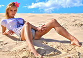 Beautiful sexual blond girl poses on the sand the sexy way in panties and t-shirt — Stock Photo