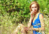Sexual elegant blond girl in blue dress sits in the wood — Stock Photo